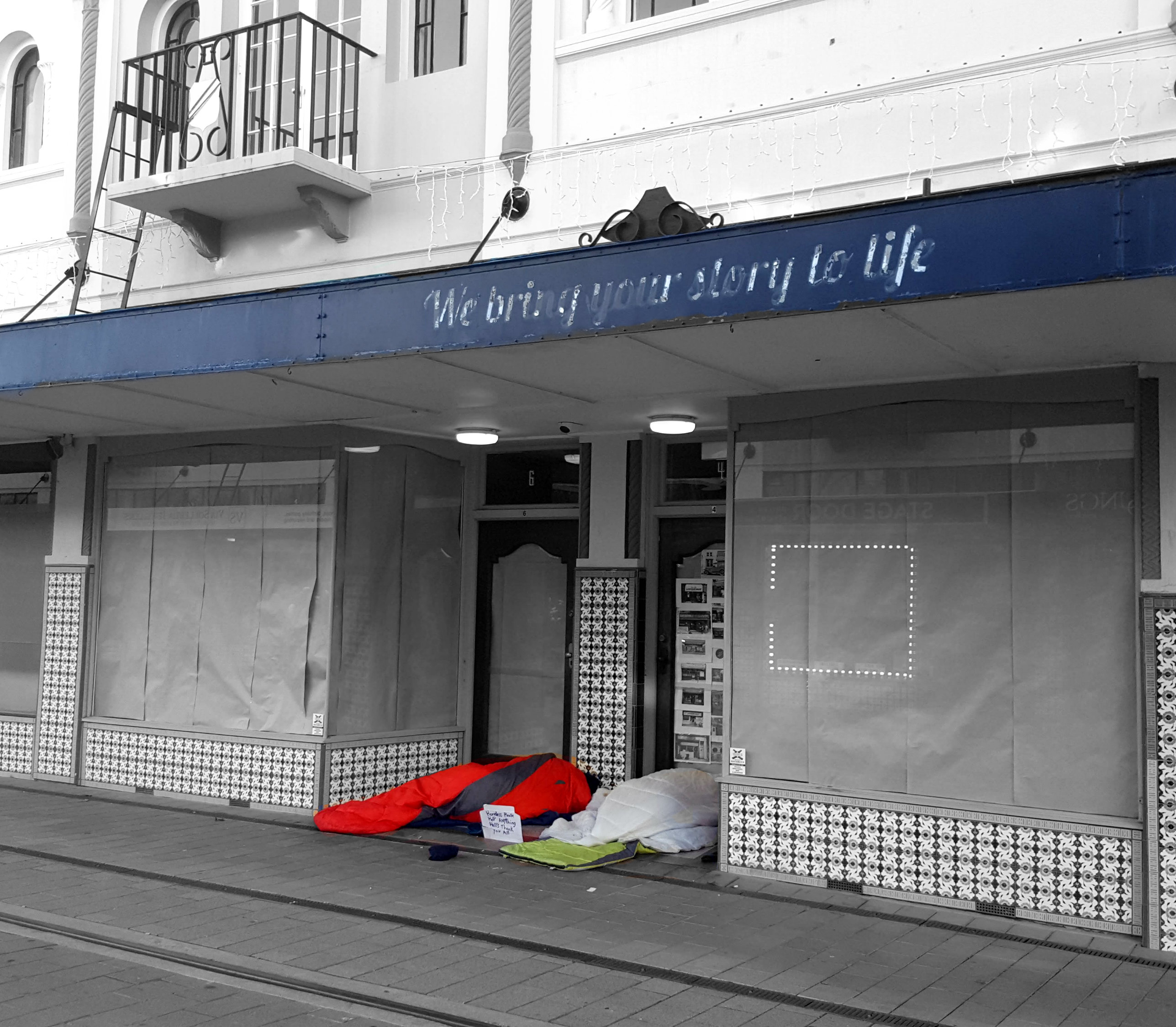 "Black and white photo with two people culred up in sleeping bags in the doorway of a boarded up shop with the words ""The story of my Life"" above."