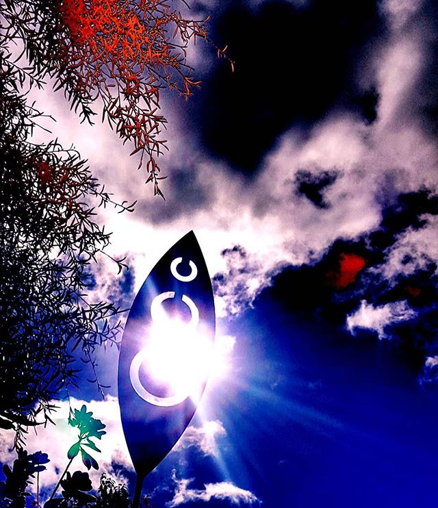 sun shining through a garden ornament that looks a bit like a spear head. Set against blue sky and clouds. Edited so that it is deep blue, white and red.