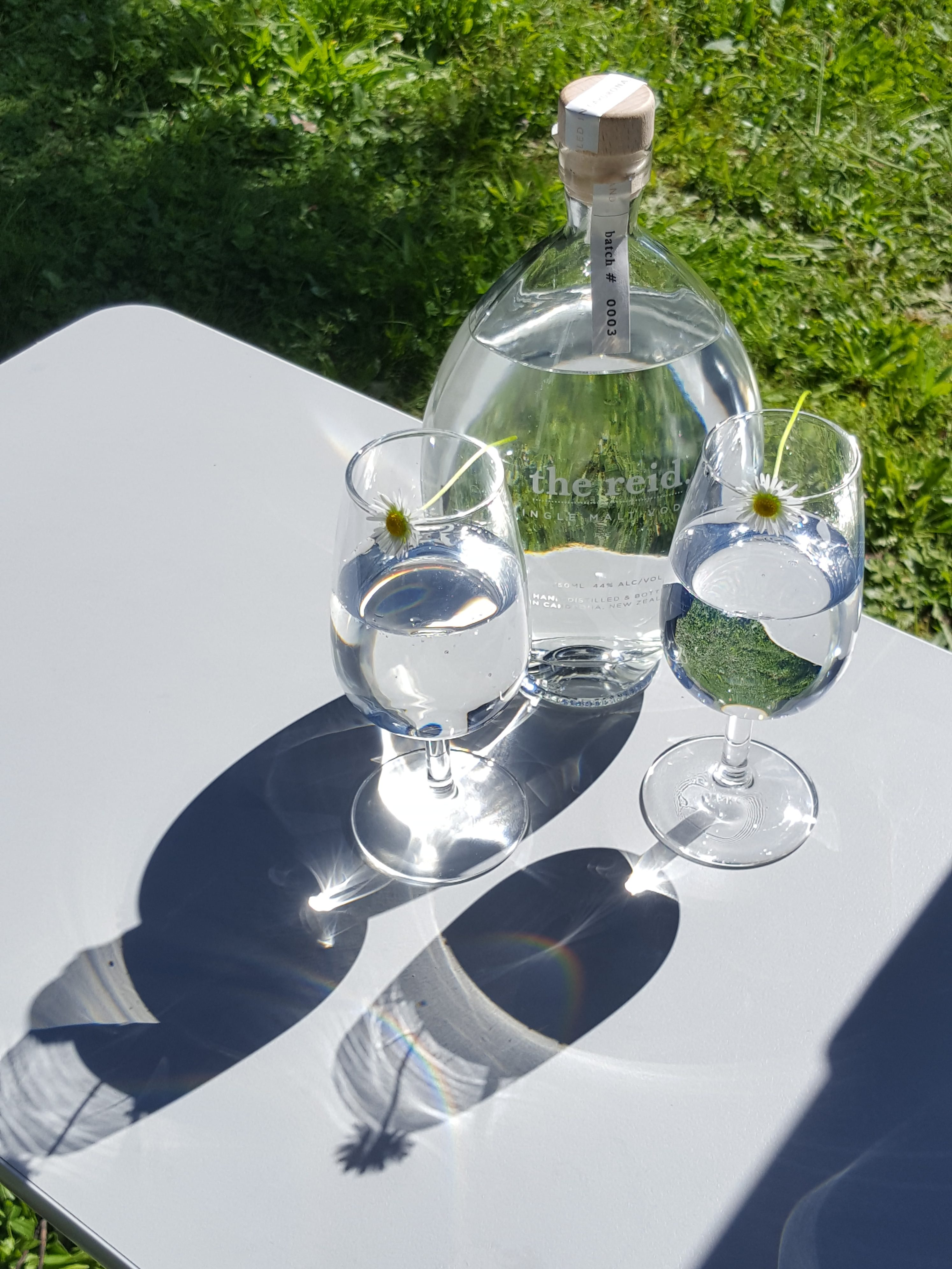 clear glass bottle and two glasses with clear liquid in, castig shadows in the sunlight on a grey table