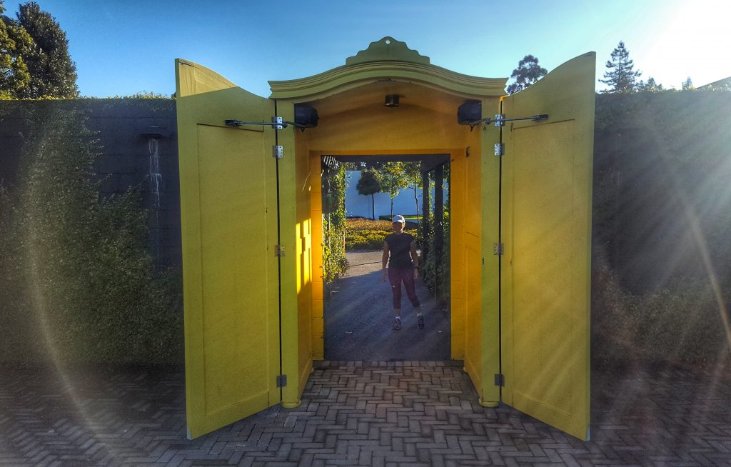 Looking through a doorway with large yellow doors. Through the doorway you can see a woman with gardens beyond