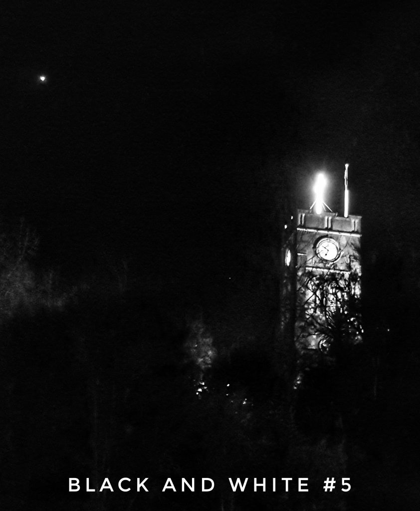 A church tower on the right brightly lit in a dark night