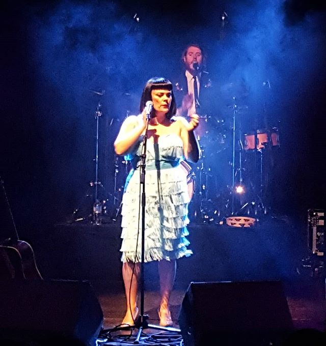 a female singer wearing a very pale blue dress at the microphone singing. The background is an inky blue and you can just see one of the band members in the haze of the lights.