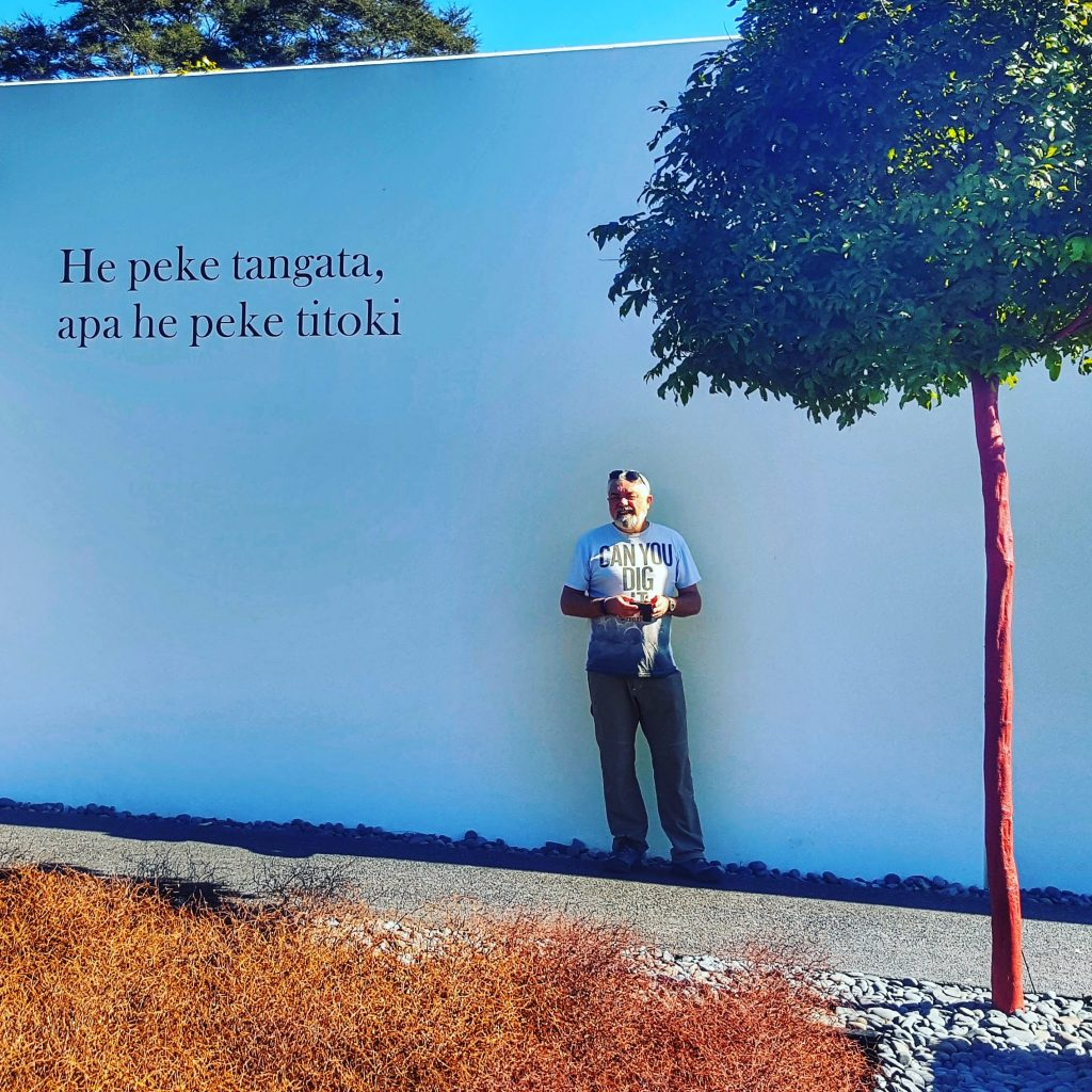"man standing against a white wall with the words He peke tangata, apa he peke titoki' written on it. That means ""The human family lives on while the branch of the titoki falls and decays."
