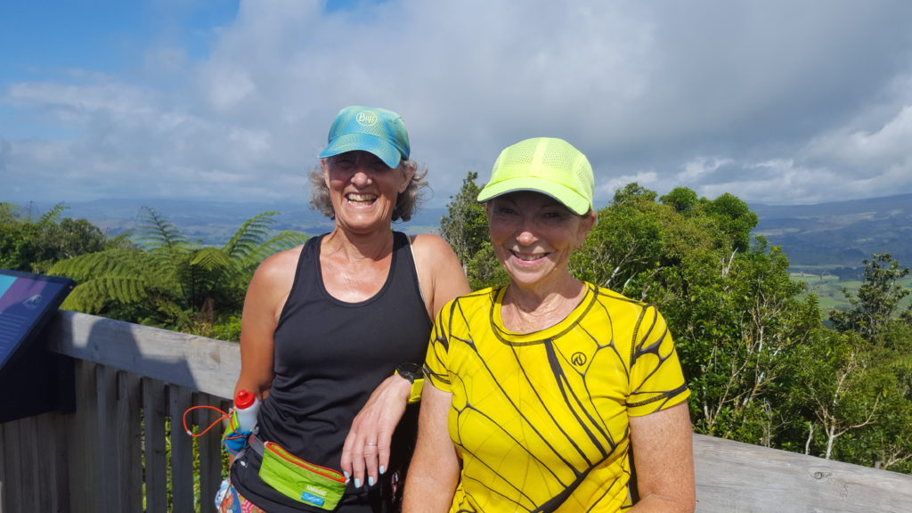 Two women of a certain age wearing running gear standing in the top of a wooden structure that marks that summit of a hill. It is bright and sunny so they are wearing caps. Behind them there are mountains and green rolling fields and hills which you can see through the canopy of trees.