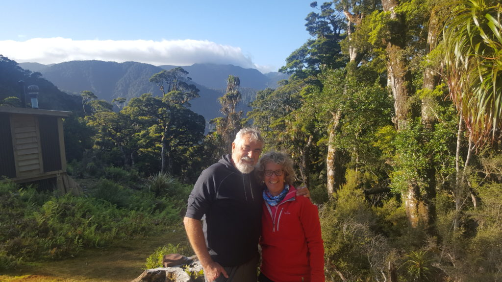 A man has his arm around a woman's shoulder - clearly they are a couple. They look happy and content. They are standing in the evening sun at the top of a mountain. There are trees around them, to the left a wooden hut and in the distance a mountain range. A white cloud sits above the mountains with blue sky above the cloud.