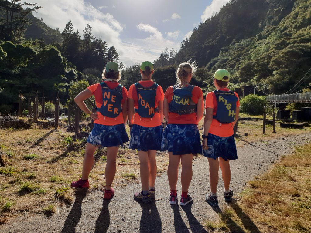 4 women wearing running gear in the countryside, facing away from the camera in a row. They have backpacks which have the words Never, Again, Yeah, Right written on them. This is their team name.