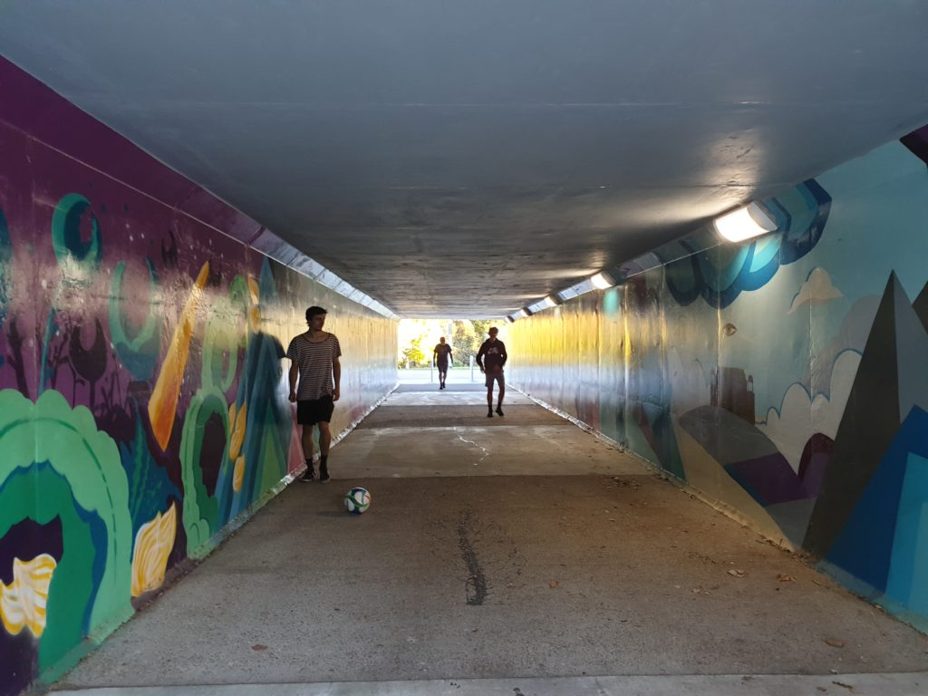 Boys playing football in an underpass