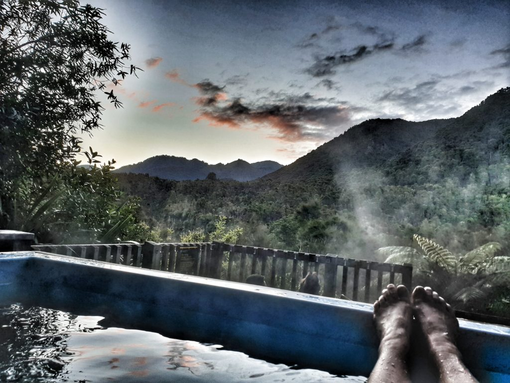 a foot sticks out of the corner of a hot pool set in the bush. The sun is setting over the mountains in the distance so the clouds are tinged with pink