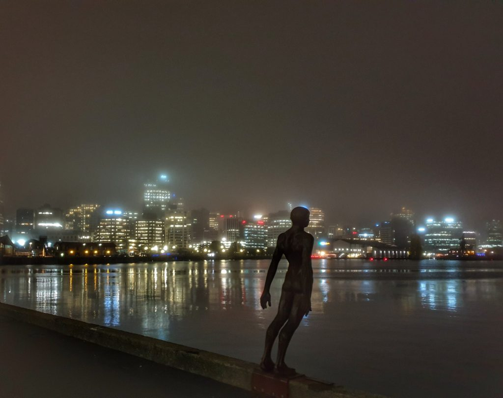 statue of a man looking as if he is about to dive in the water. The lights of the city shine through the mist and darkness in the background