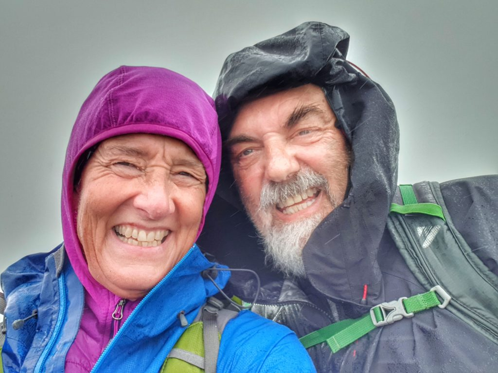 a man and a woman wearing wet weather gear smile despite the wet weather