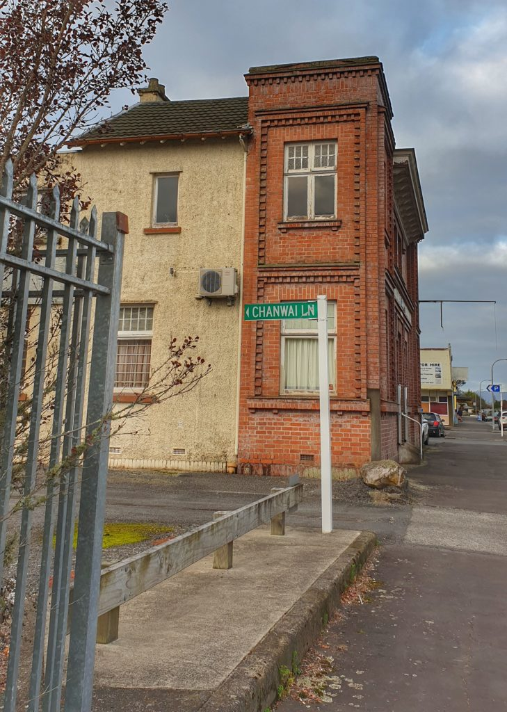 Street in a small town in New Zealand. A street sign points the way down a road in front of a red brick building