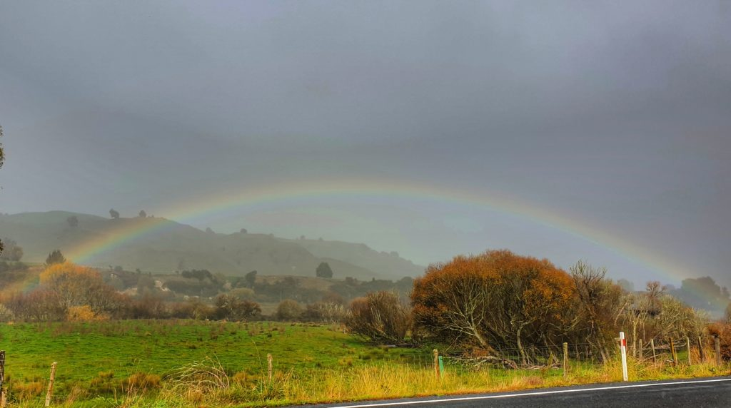 rainbow over a grey rural landscape