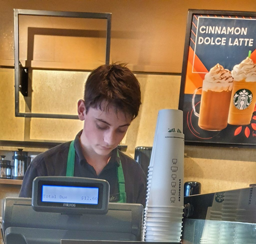 young man behind a counter in a coffee shop