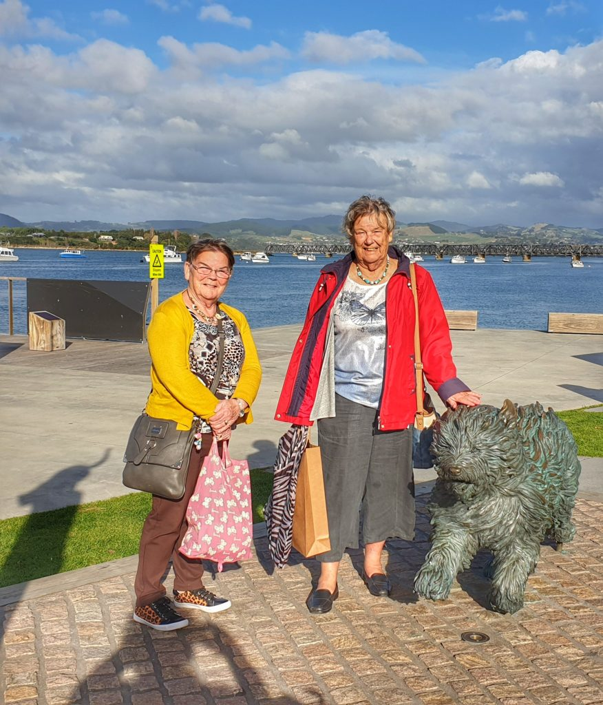 Two sisters standing in front of ocean and a sculpture of a dog