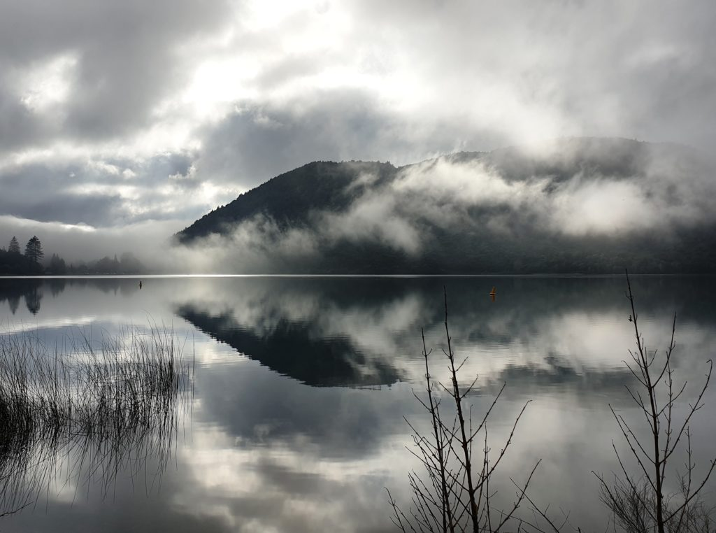 light clouds hang around a mountain both are reflected in a lake