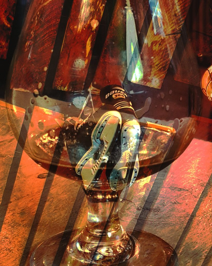 a pair of ice skates inside a glass of beer