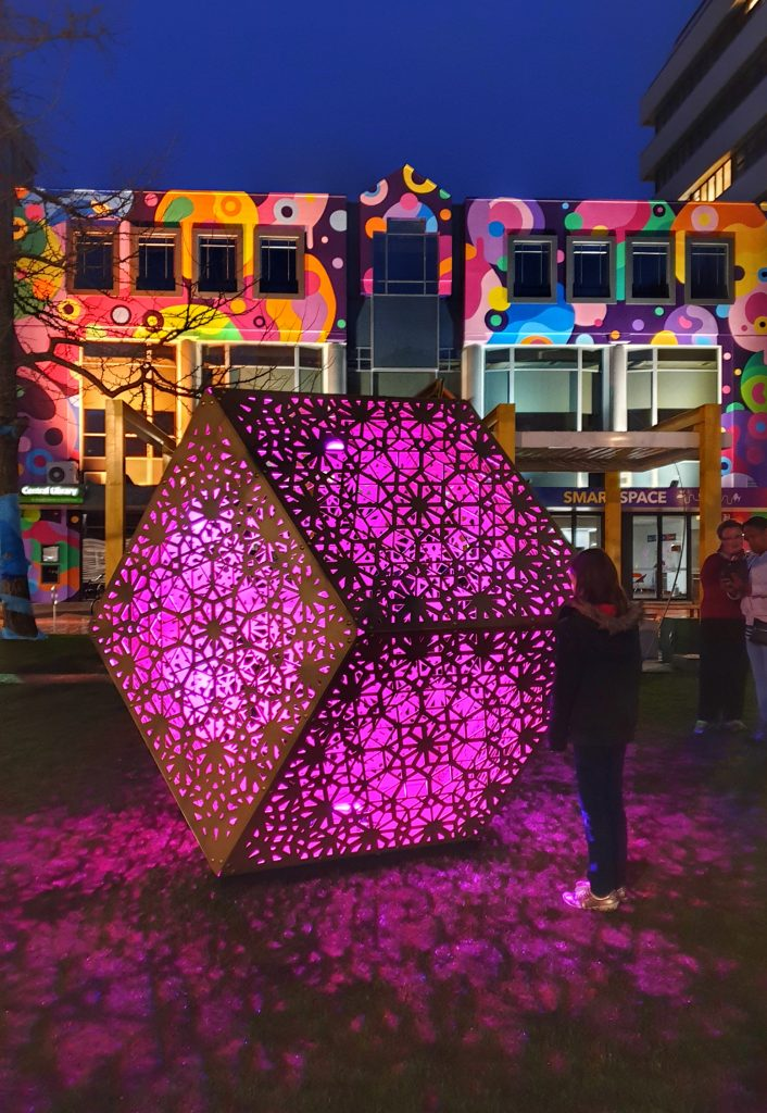 giant geodesic cube lit up in pink in front of the painted wall of the library