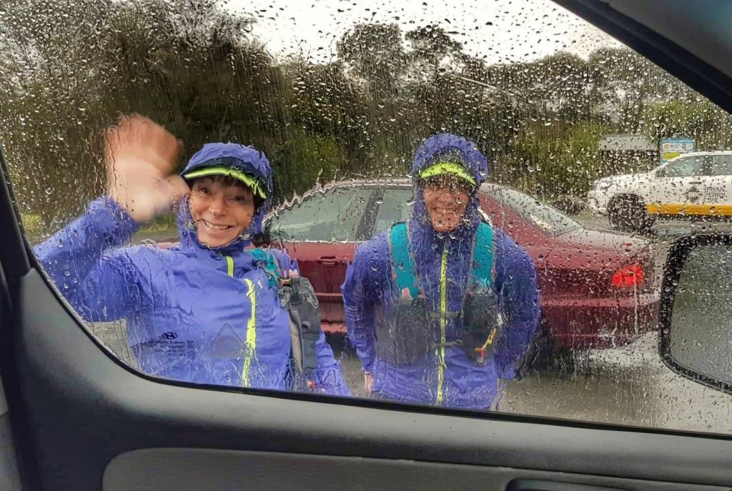 two rain jacket clad women wave through a rain spattered car window at someone inside