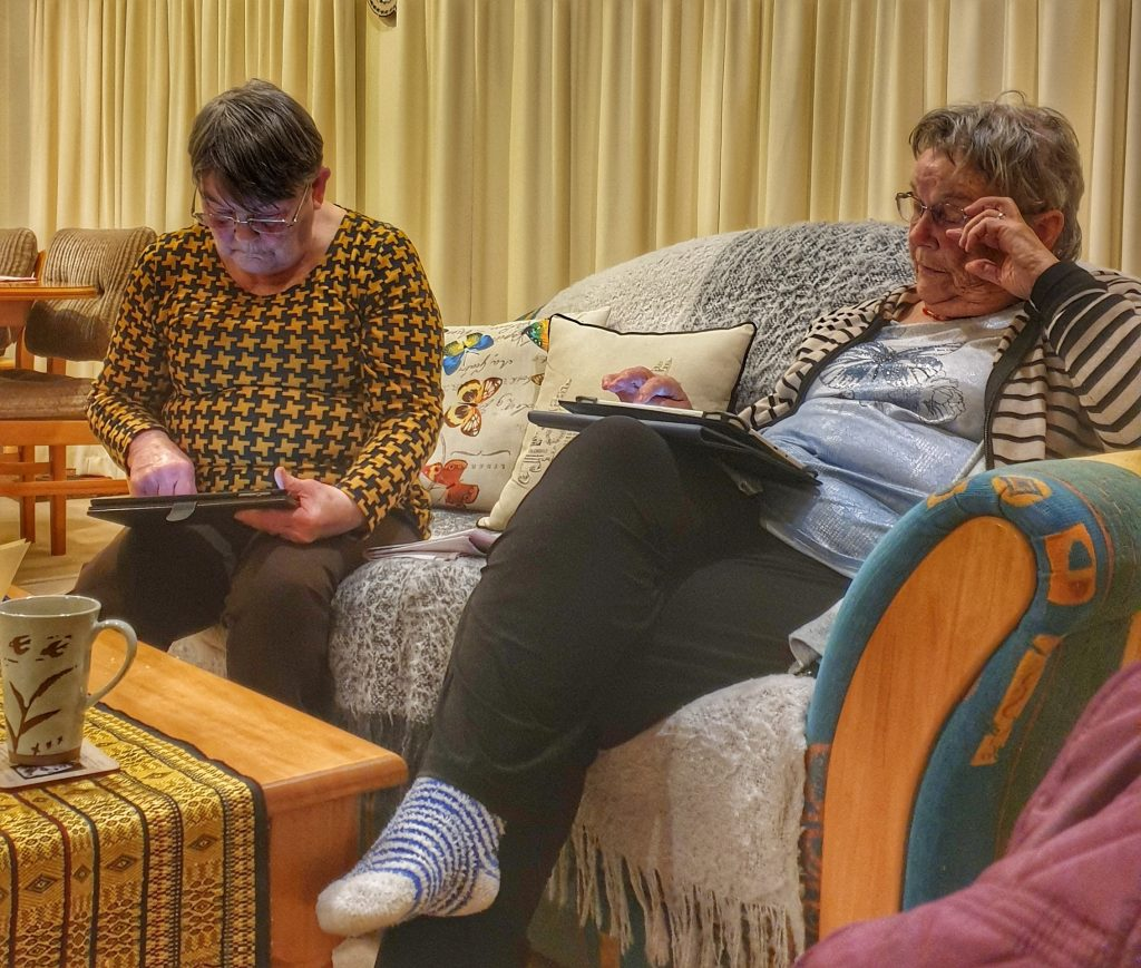 twoi elderely ladies playing games on their mobile devices in a living room