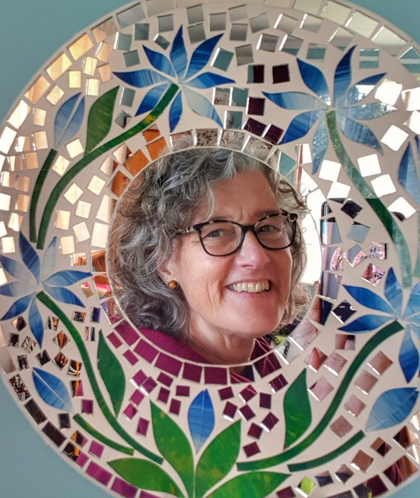reflection of a grey haired smiling woman in a mosaic mirror