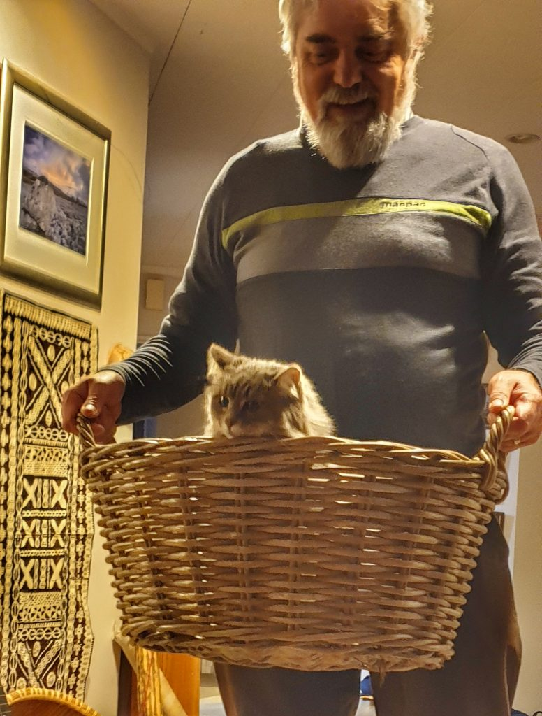 man holding a basket with a cat in it