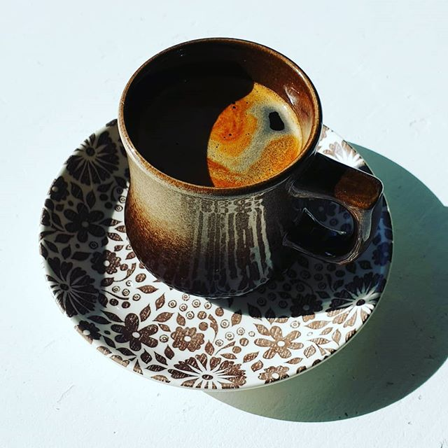 a brown cup fullof rich dark, black coffee on a white saucer with brown floral pattern.