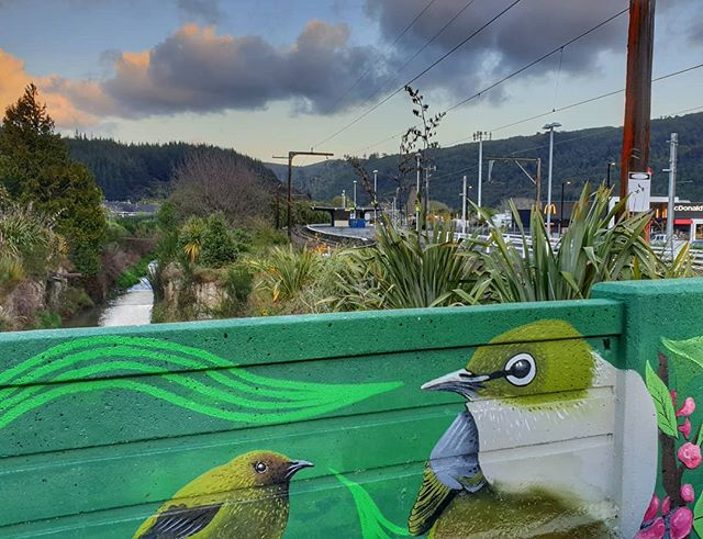 a low wall painted with flora and fauna gives way to a railway station behind it