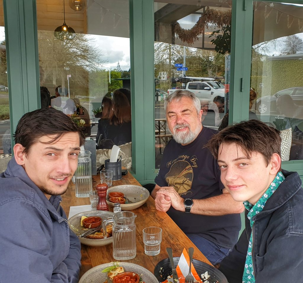 a father and two sons sit at an outside table of a cafe