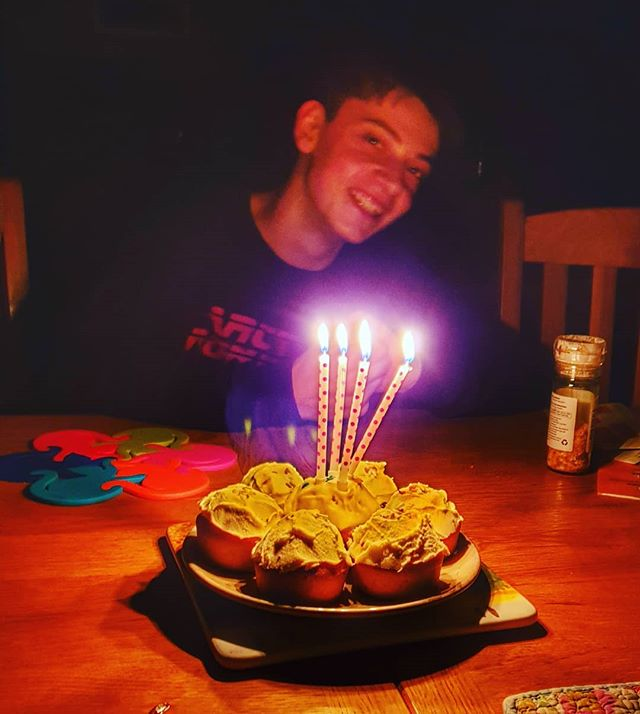 a young man smiles from behind a cake with lighted candles