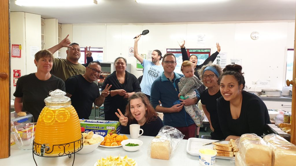 a group of happy looking people in a large kitchen. on the bench in front is food laid out for breakfast