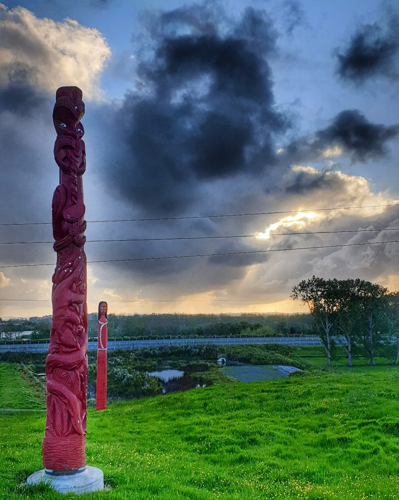 a red carved Māori pou stands in a field with grey clouds floating in a blue sky