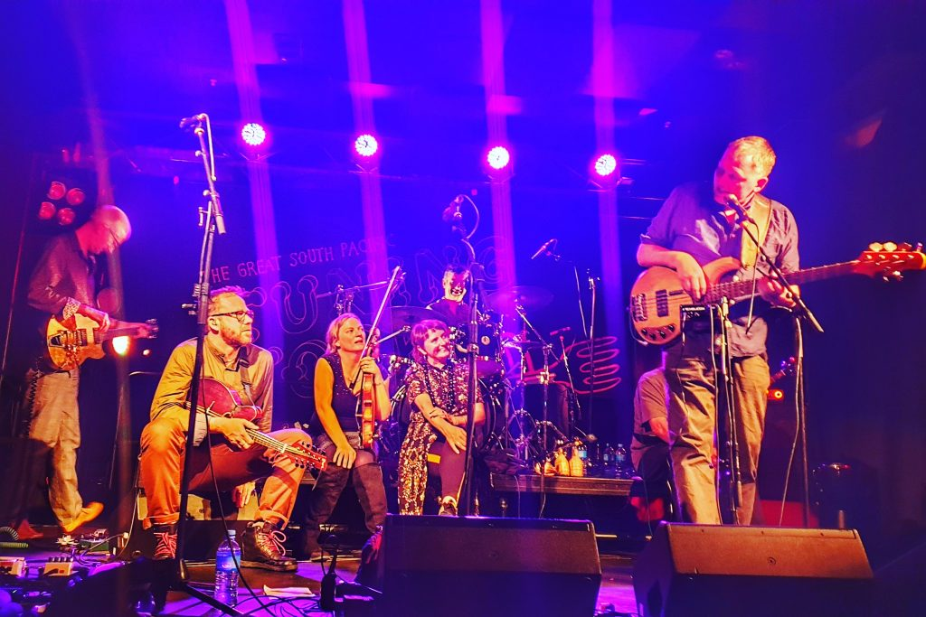 a band on stage. 3 members are sitting listening wjile a fourth is standing telling a story
