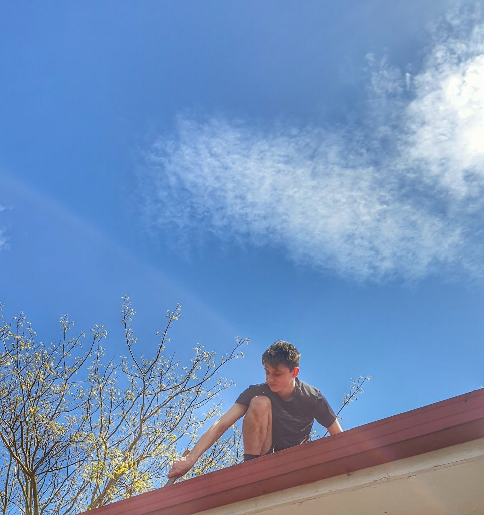a young man on a roof cleaning out the gutters