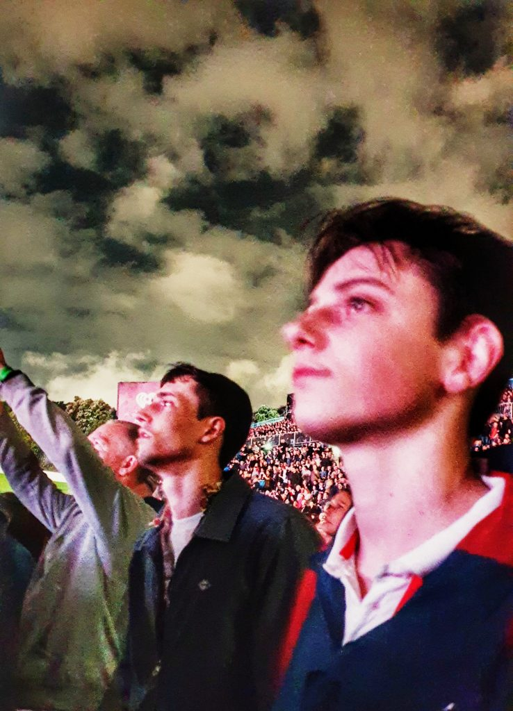 two young men looking upwards and outwards in a crowd. A dark cloudy sky in the background