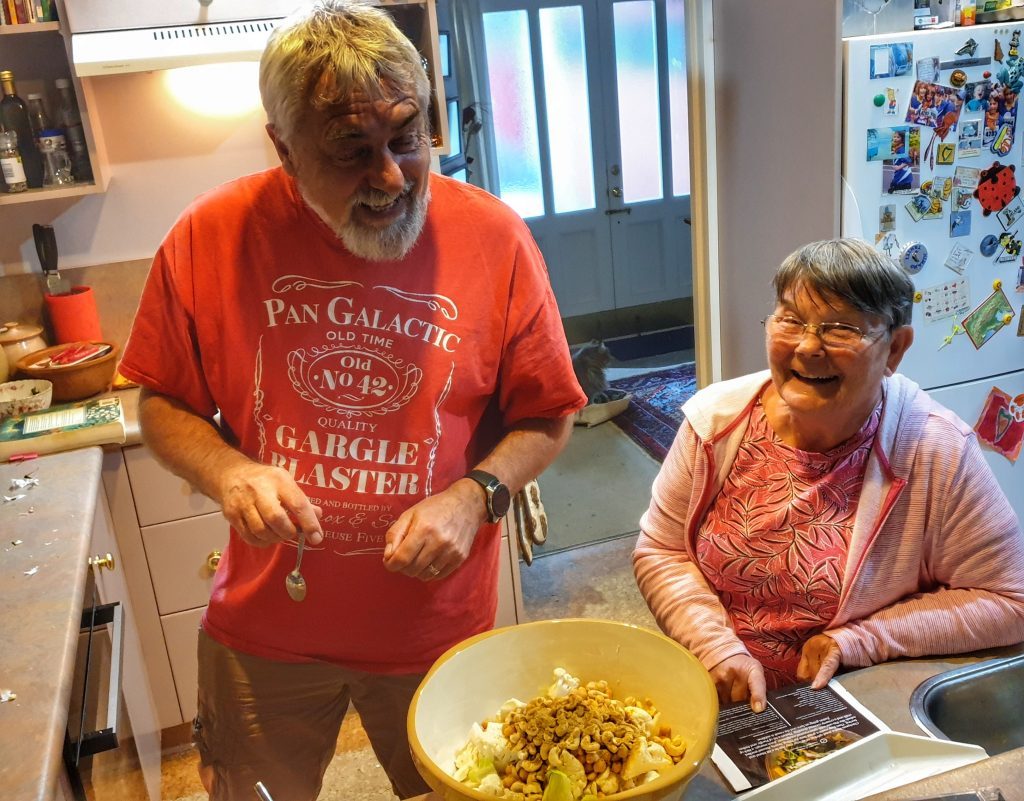 a bearde man n a red teeshirt laughing with a small woman (Nephew and Aunt) they are cooking in the kitchen
